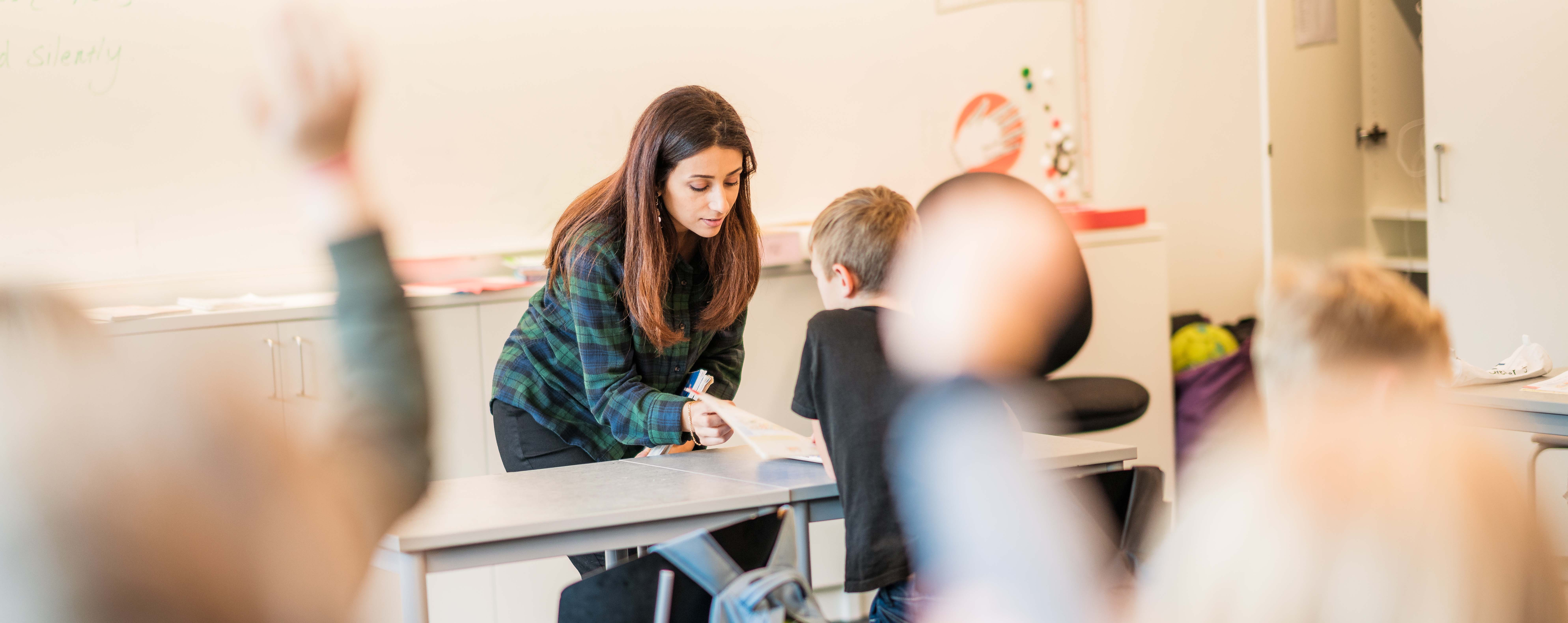 d06f9c5491ae En bild från ett klassrum med en lärare och elever som räcker upp handen i  förgrunden